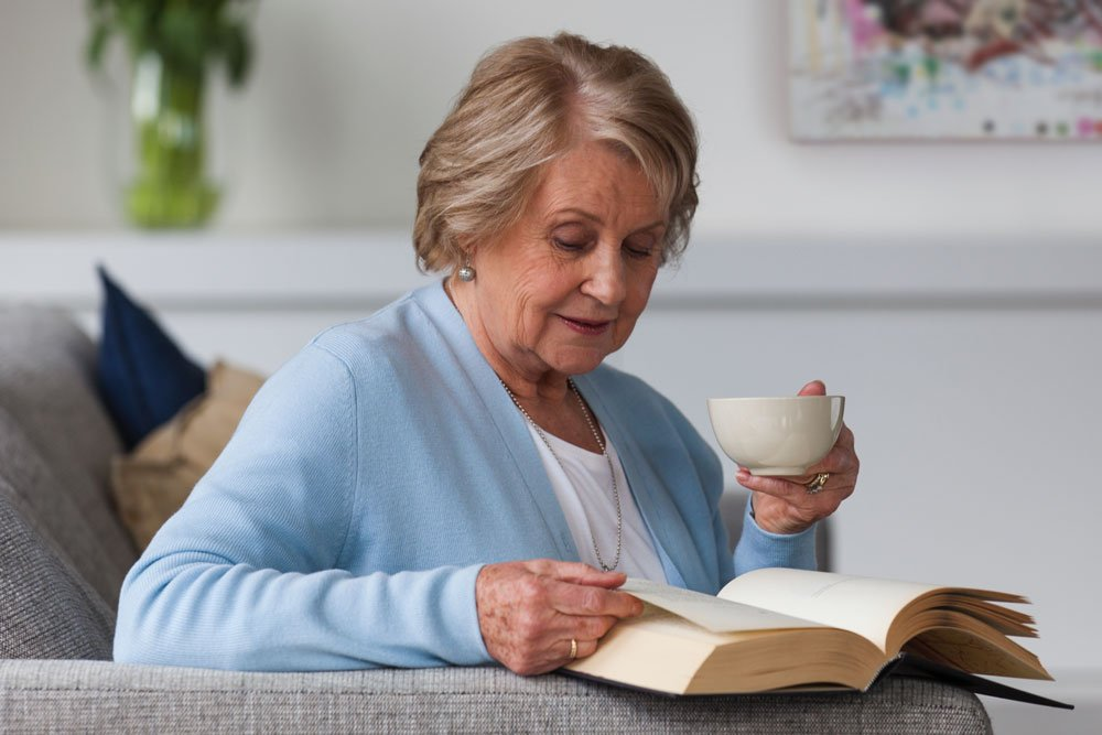 Senior woman drinking tea and reading a book, The Orchards